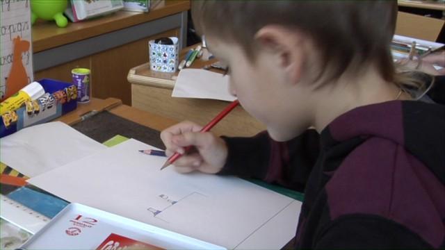 Un élève qui dessine un physicien