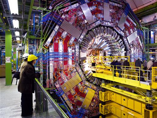 Des ingénieurs, debout sur une plateforme, insèrent le trajectographe au cœur du détecteur CMS. Le détecteur semble gigantesque par rapport aux hommes.